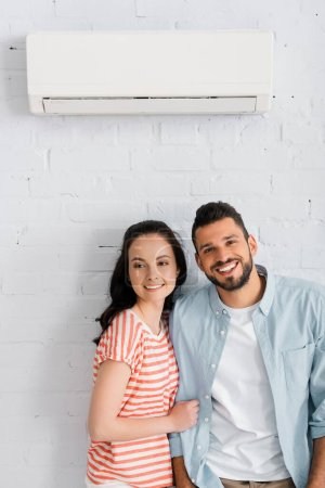 Handsome man smiling at camera near girlfriend and air conditioner on wall