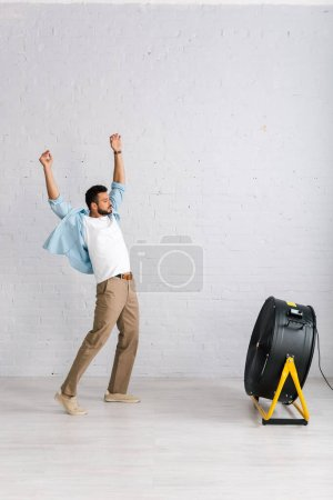 Hombre barbudo guapo de pie cerca de ventilador eléctrico en la sala de estar