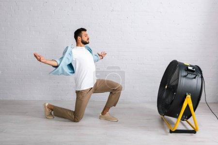 Hombre guapo de pie sobre la rodilla cerca de ventilador eléctrico en el suelo en casa
