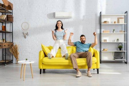 Positives Paar zeigt Daumen hoch und ja Gesten auf Couch im Wohnzimmer
