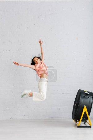 Mujer joven saltando con las manos levantadas cerca de ventilador eléctrico en el suelo en casa