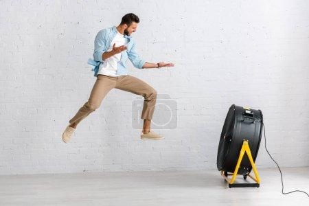 Hombre guapo saltando cerca de ventilador eléctrico en el suelo en casa