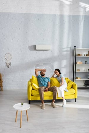 Tired couple suffering from heat on sofa in living room