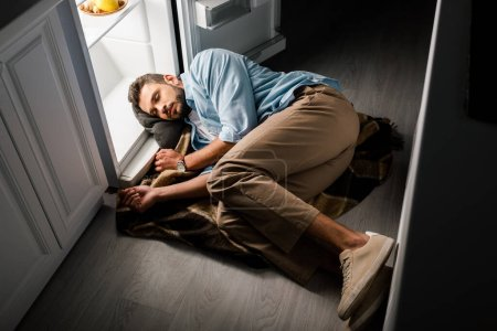 Photo for Handsome man sleeping near open fridge in kitchen at night - Royalty Free Image