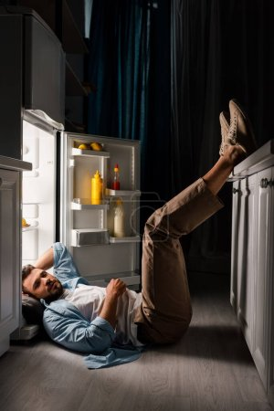 Photo for Side view of man looking at camera while lying on floor near open fridge at night - Royalty Free Image