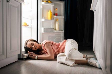 Photo pour Jeune femme dormant sur le sol près d'un réfrigérateur ouvert la nuit - image libre de droit