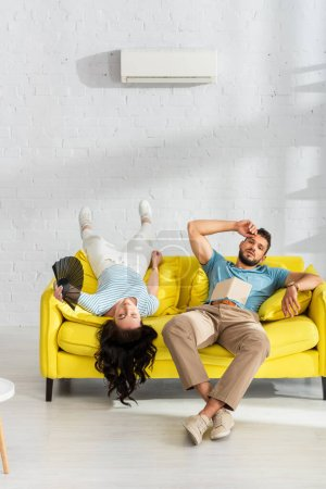 Tired couple with book and fan suffering from heat on sofa in living room