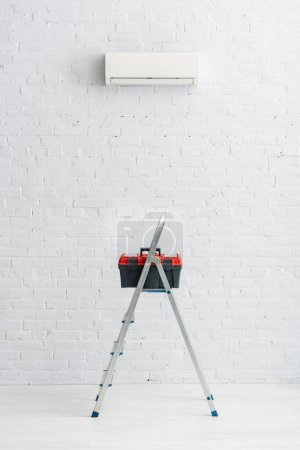 Photo for Toolbox on ladder near air conditioner on white wall - Royalty Free Image