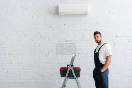 Photo for Handsome workman with hands in pockets of overalls looking at camera near toolbox on ladder and air conditioner - Royalty Free Image