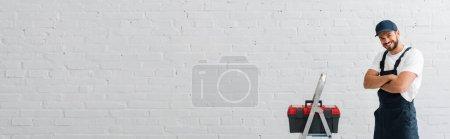 Foto de Foto panorámica de obrero sonriente mirando la cámara cerca de una caja de herramientas en escalera y pared blanca. - Imagen libre de derechos