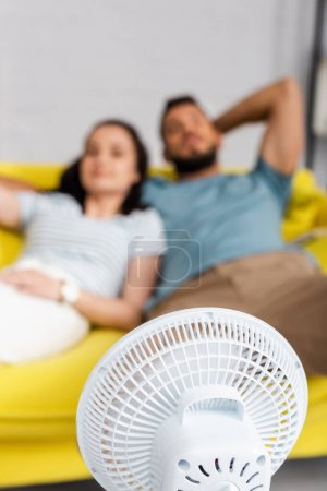 Selective focus of electric fan near couple sitting on sofa at home