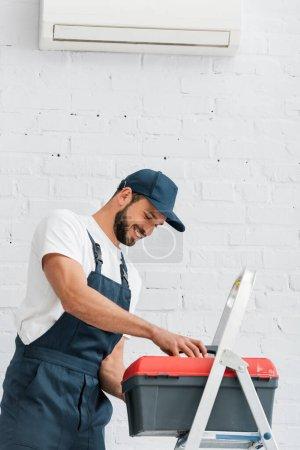 Foto de Trabajador sonriente en una caja de herramientas de sujeción uniforme cerca de escalera y aire acondicionado en la pared blanca. - Imagen libre de derechos