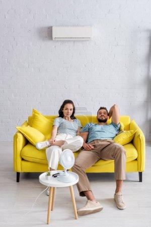 Selektiver Fokus eines jungen Paares, das in der Nähe eines elektrischen Ventilators auf dem Wohnzimmertisch in die Kamera blickt