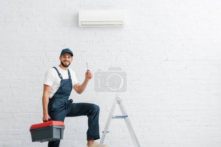 Photo pour Travailleur souriant en uniforme tenant tournevis près de l'échelle et climatiseur sur le mur - image libre de droit