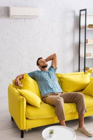 Photo pour Beau homme tenant télécommande du climatiseur sur le canapé dans le salon - image libre de droit