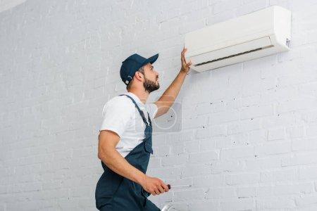 Photo pour Vue latérale de l'ouvrier en tenue de travail tournevis près du climatiseur - image libre de droit
