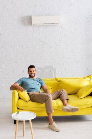 Photo pour Beau homme souriant à la caméra tout en tenant télécommande du climatiseur à la maison - image libre de droit