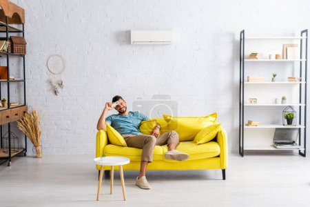 Photo for Positive man holding remote controller of air conditioner and smiling at camera on sofa at home - Royalty Free Image