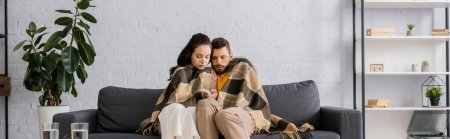 Photo for Panoramic crop of couple wrapped in plaid holding remote controller of air conditioner on sofa - Royalty Free Image