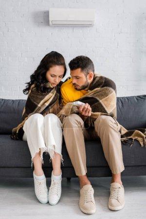 Photo pour Jeune homme tenant télécommande du climatiseur tout en se sentant froid près de la petite amie sur le canapé à la maison - image libre de droit