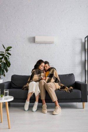 Photo pour Couple enveloppant en plaid et tenant télécommande du climatiseur tout en se sentant froid sur le canapé - image libre de droit