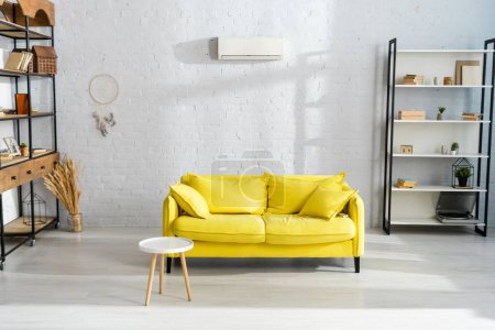 Interior of living room with coffee table near yellow couch