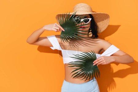 Photo pour Fille à la mode en maillot de bain, lunettes de soleil et chapeau de paille tenant feuilles de palme sur orange - image libre de droit