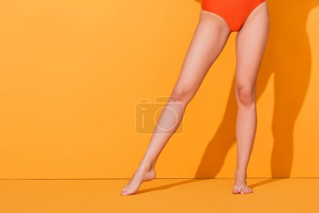 Photo for Cropped view of barefoot woman in swimsuit standing on orange, summer concept - Royalty Free Image