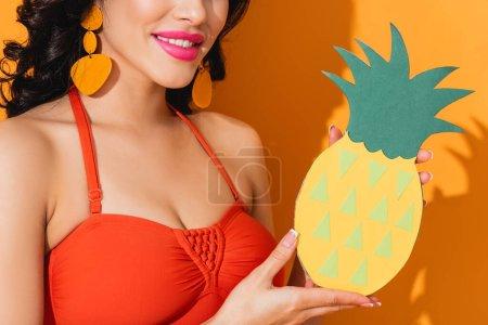 Photo pour Vue recadrée de femme heureuse en maillot de bain tenant de l'ananas coupé en papier sur orange - image libre de droit