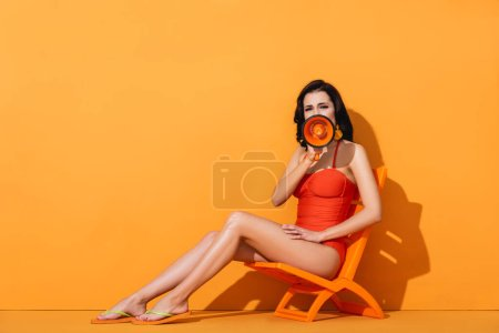 Photo for Woman in swimwear holding megaphone and screaming while sitting on deck chair on orange - Royalty Free Image