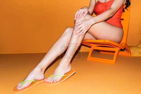 Photo pour Vue recadrée de la jeune femme en maillot de bain toucher la jambe tout en étant assis sur la chaise longue sur orange - image libre de droit