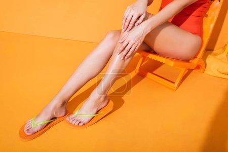 Photo pour Vue recadrée de la femme en maillot de bain touchant la jambe tout en étant assis sur la chaise longue sur orange - image libre de droit
