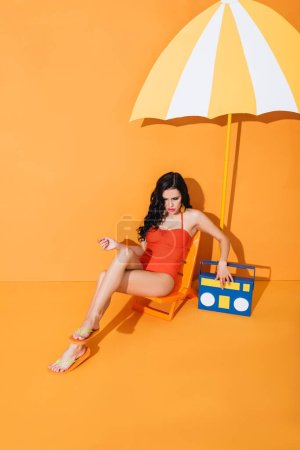 young woman in swimsuit touching paper boombox while sitting on deck chair near umbrella on orange