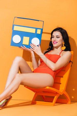 femme heureuse en maillot de bain tenant la boombox en papier tout en étant assis sur la chaise longue sur orange