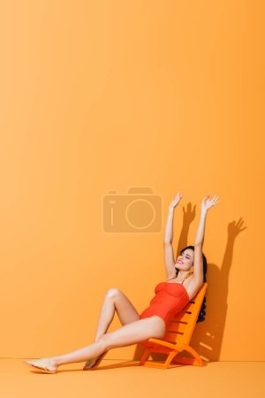 happy girl with hands above head sitting on deck chair on orange