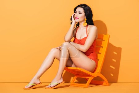 Photo for Happy woman in swimsuit sitting on deck chair and looking away on orange - Royalty Free Image
