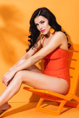 Photo pour Attrayant jeune femme en maillot de bain assis sur la chaise longue et regardant la caméra sur orange - image libre de droit