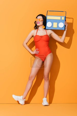 Photo for Happy woman in sneakers, sunglasses and bathing suit holding paper cut boombox while standing with hand on hip on orange - Royalty Free Image