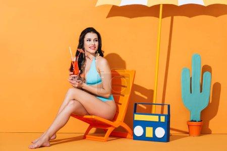 Photo pour Femme heureuse en maillot de bain assis sur la chaise longue près de la boombox en papier, cactus et parapluie tout en tenant un cocktail sur orange - image libre de droit