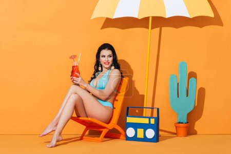 Photo for Cheerful woman in swimwear sitting on deck chair near paper boombox, cactus and umbrella while holding cocktail on orange - Royalty Free Image