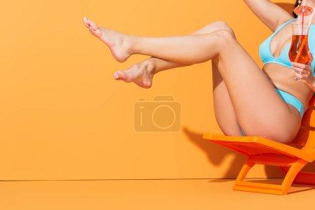 Photo pour Vue recadrée de la femme avec les pieds nus assis sur la chaise longue et tenant cocktail sur orange - image libre de droit