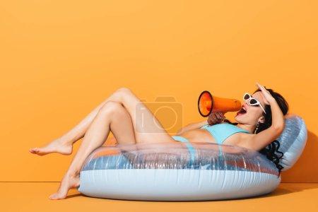 Photo pour Jeune femme en maillot de bain couché sur anneau gonflable et criant en mégaphone sur orange - image libre de droit