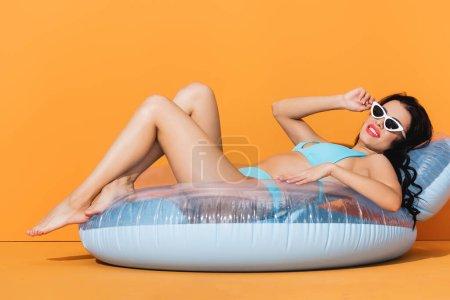 Photo pour Femme heureuse en lunettes de soleil et maillots de bain couché sur anneau gonflable sur orange - image libre de droit