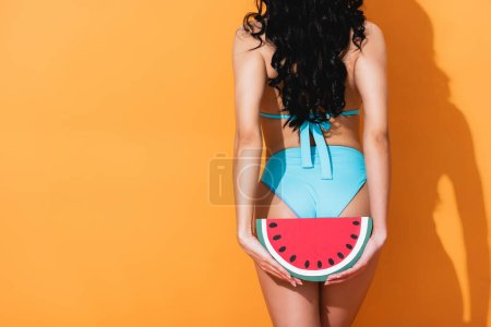 Photo for Back view of girl in swimwear standing and holding paper watermelon on orange - Royalty Free Image
