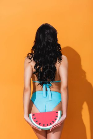 Photo for Back view of woman in swimwear standing and holding paper watermelon on orange - Royalty Free Image