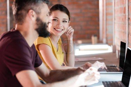 enfoque selectivo de la mujer de negocios feliz mirando a hombre de negocios cerca de computadoras portátiles en la oficina