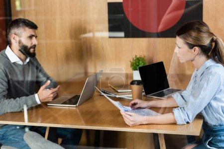 Photo pour Femme d'affaires tenant journal près homme d'affaires barbu et ordinateurs portables - image libre de droit