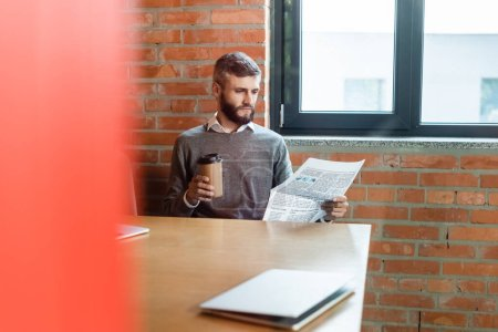 Photo for Selective focus of bearded businessman holding coffee to go and reading newspaper near laptop - Royalty Free Image