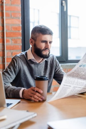 selective focus of bearded businessman holding coffee to go and reading newspaper
