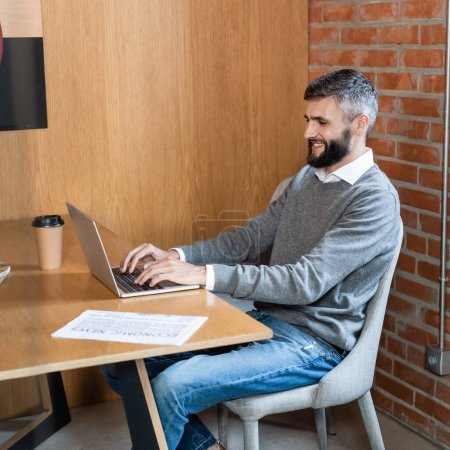 handsome businessman smiling while using laptop near newspaper and paper cup